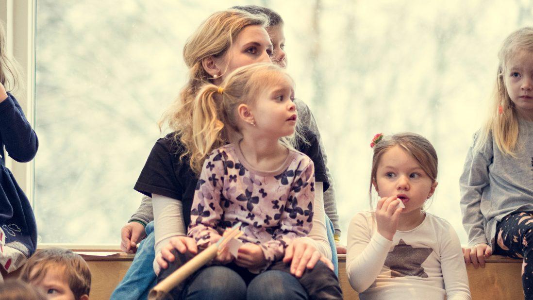 Jente sitter på fanget til ansatt i en samlingsstund i barnehagen. Flere barn sitter ved siden av.