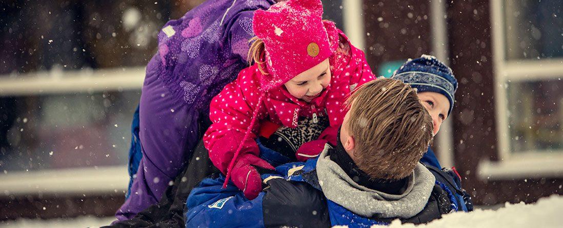 Mannlig barnehageansatt leker i snøen med tre barn.