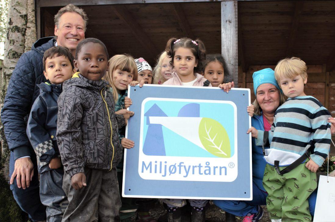 Barnehagebarn og ansatte står rundt et Miljøfyrtårnskilt