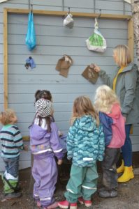 Barnehagebarn og en voksen ser på søppel som er hengt opp på en yttervegg