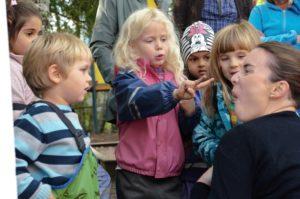 Barnehagebarn snakker med en dame som sitter på huk