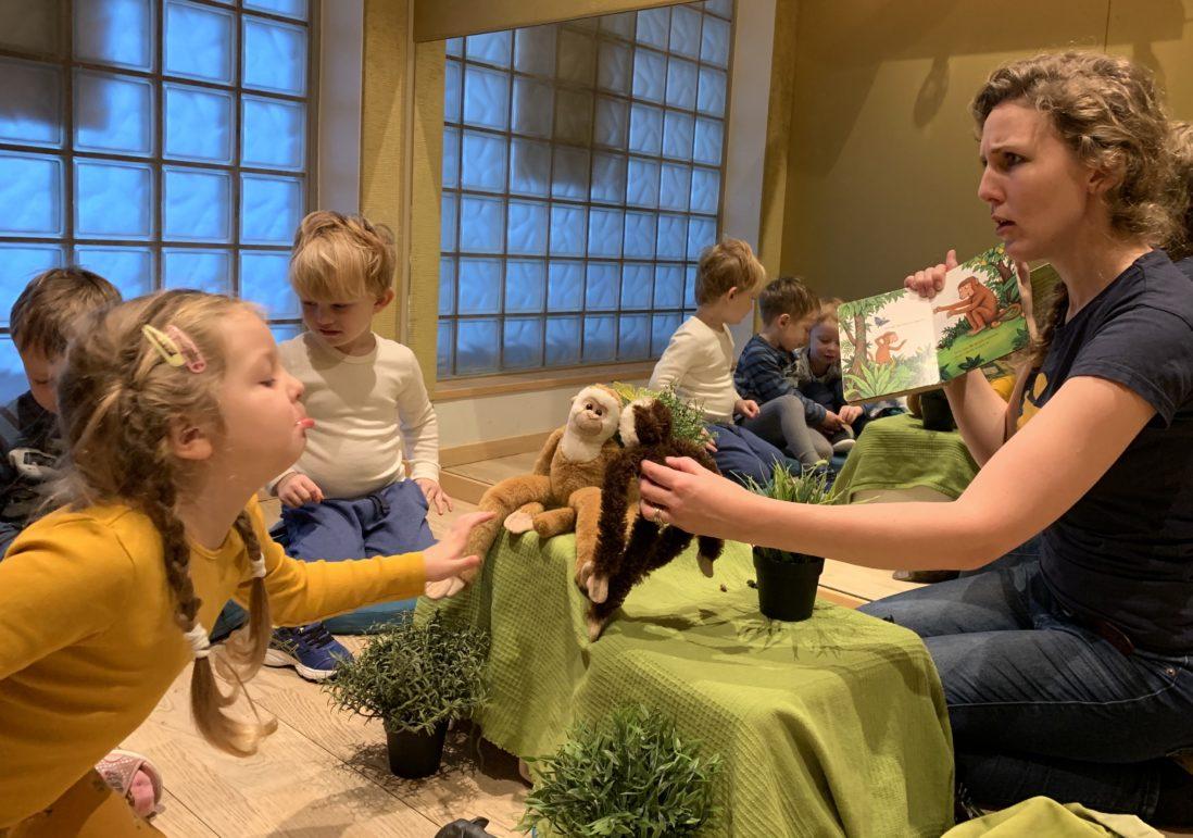 En barnehageansatt leser en bok for en gruppe med barn