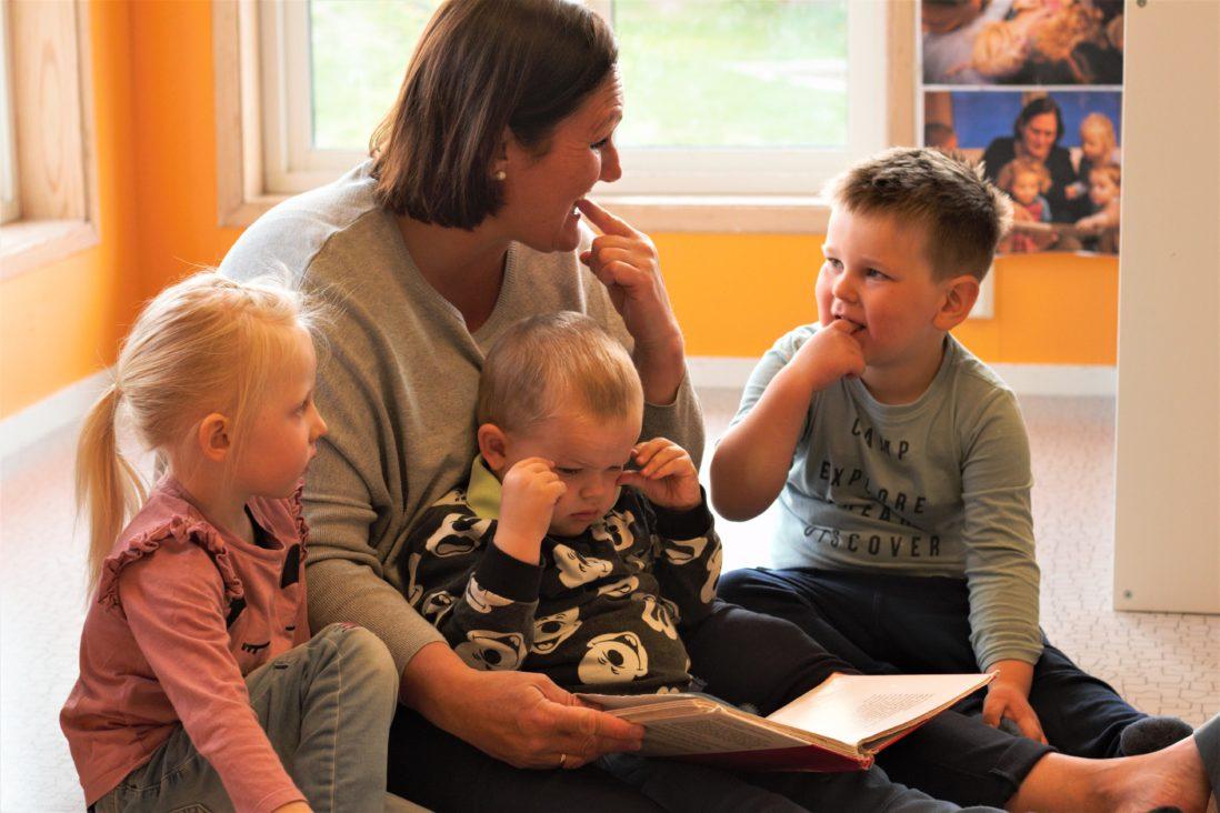 Barnehageansatt leser bok for barn