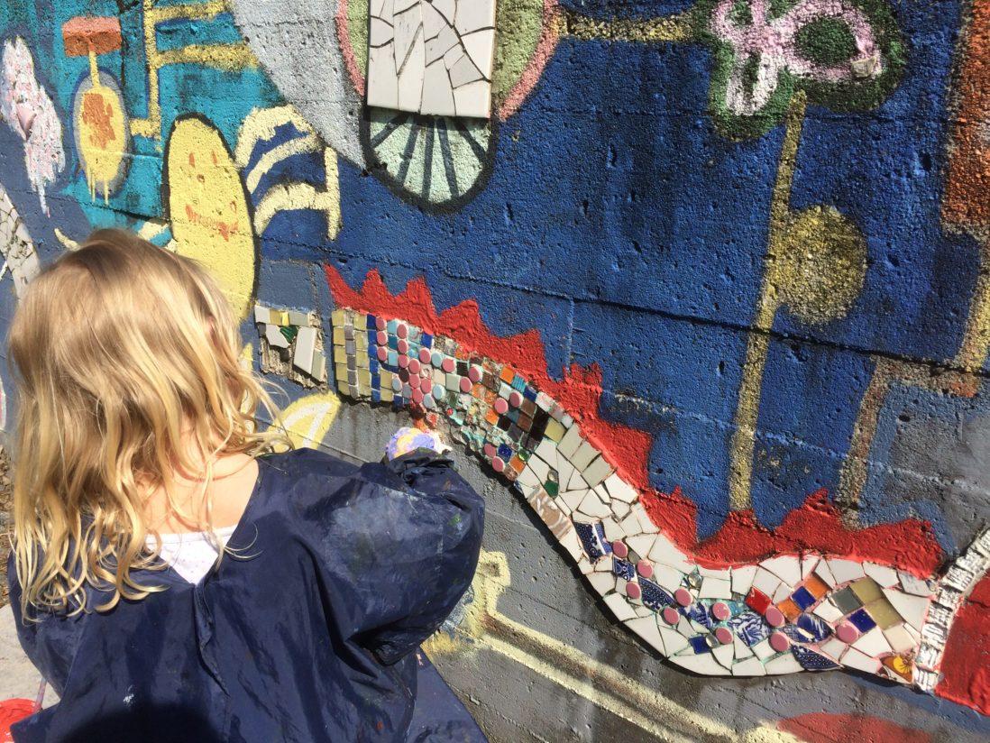 Barn dekorerer en murvegg