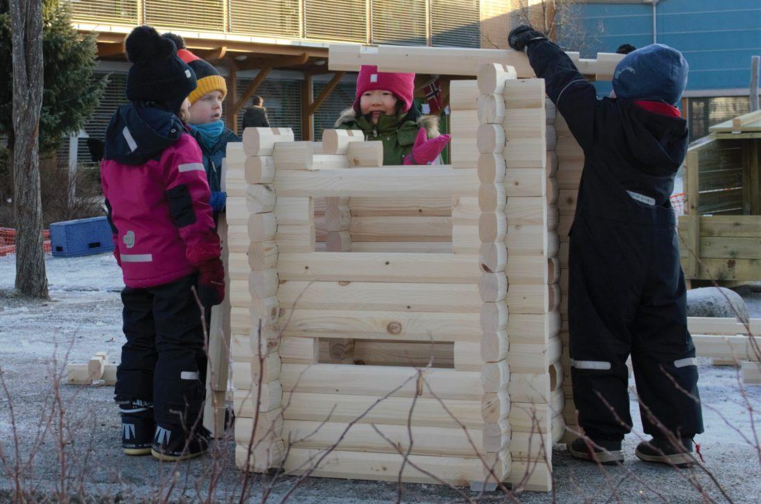 Barnehagebarn bygger et hus ved hjelp av laftetømmer.