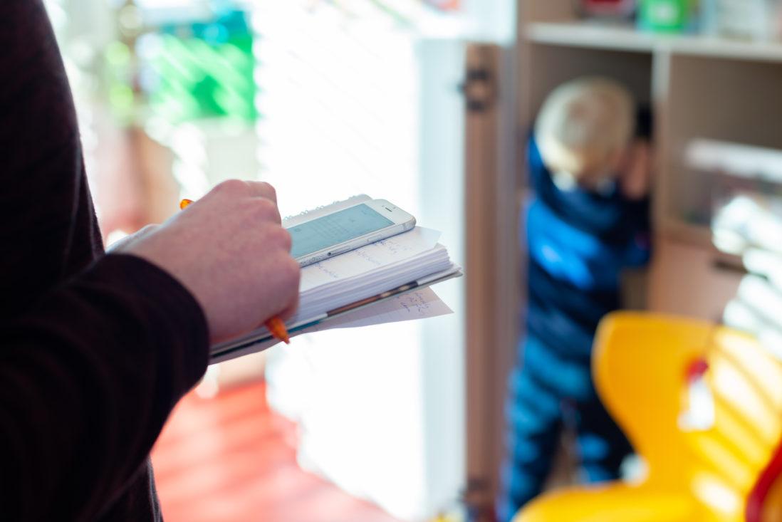Mann i en barnehage noterer mens et barn leker